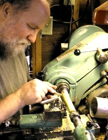 [Photo of Casey Burns turning a boxwood flute foot joint at the lathe]