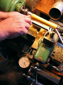 [turning a boxwood flute foot joint at the lathe]